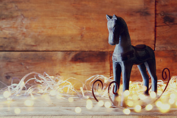 double exposure image of rocking horse and magic christmas lights on wooden table