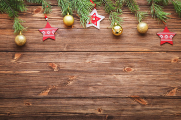 Christmas decorative stars and balls and fir branches on wooden background