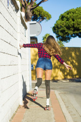 Back view of young woman in shorts on roller skates