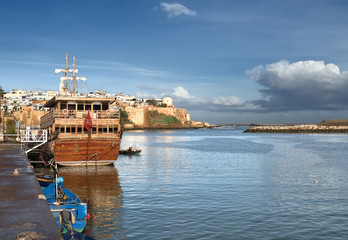 Sailing ship near the pier and the boat (even with the fishermen) on the background of the old fortress and buildings made of white stone (Sali, Morocco), and sky with clouds