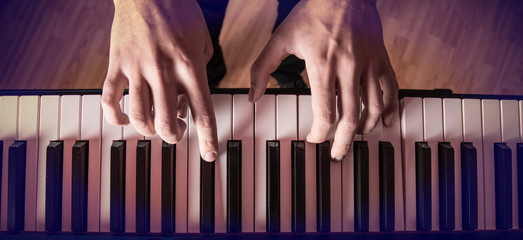 Man's hand playing piano.