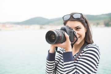 Happy woman on vacation photographing with a dslr camera on the beach and smiling