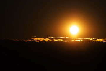 Orange solar disk and clouds closeup