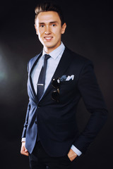 young pretty business man standing pointing in sunglasses on black background, modern hairstyle close up