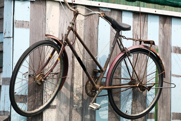 classic bicycle hanging on wooden wall.