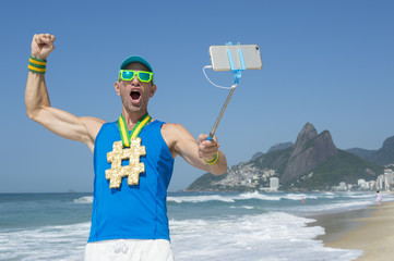Hashtag gold medal athlete punching the air as he poses for a picture with his mobile phone on a selfie stick on Ipanema Beach in Rio de Janeiro, Brazil