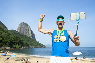 Hashtag gold medal athlete posing for a selfie with his mobile phone on a selfie stick at Praia Vermelha Red Beach in Urca, Rio de Janeiro, Brazil