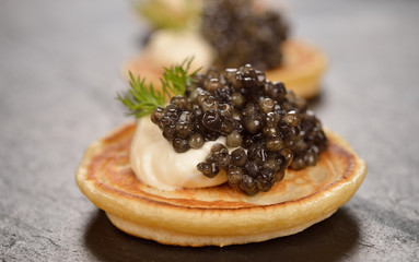 Mini pancakes with black caviar