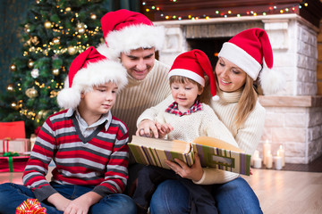 Family look at photo album together near Christmas tree in front of fireplace