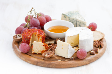 cheeses and snacks on a wooden board on white table