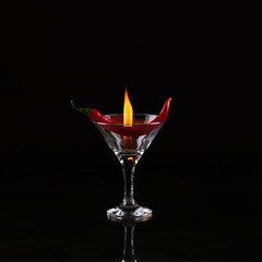 Burning alcoholic drinks with ice cubes, on black background