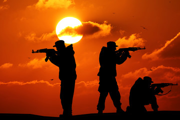 Silhouette of military three soldier or officer with weapons at sunset. shot, holding gun, colorful sky, mountain, background, team