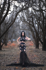 Beauty gothic woman in sexy dress in the forest