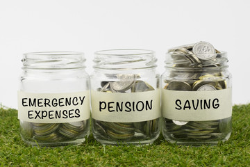 Coins in glass jar contains coins for emergency expenses, pension and saving. financial concept