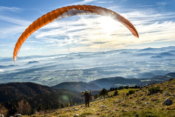 Paraglider is starting off a mountain