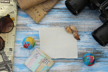Creative travel background - binoculars, sunglasses, notebook, globe and decoration