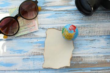 Creative travel background - binoculars, sunglasses, notebook, globe and decoration