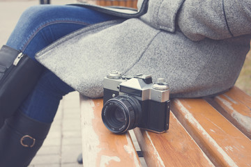 woman sitting and next old camera
