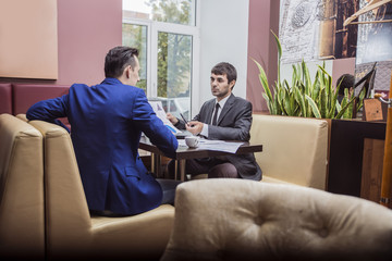 two businessmen communicate happily negotiating in the cafe