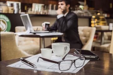 Бизнесмен работает в кафе, а перед ним на столе лежат атрибуты делового человека - очки, ручка и деловые бумаги.