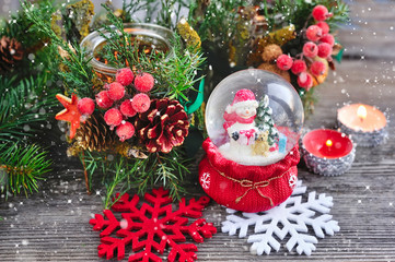 A snow globe with snowman and christmas candle with branches of fir
