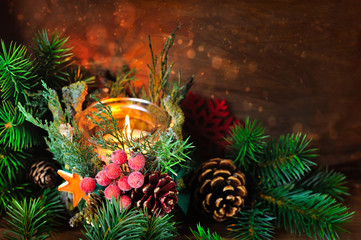 Candlestick and Christmas tree branches on a wooden background.