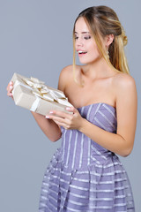 Portrait of an adorable woman in gala dress holding beautifully wrapped present box