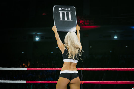 beautiful sexy girl in ring during competition in MMA and Boxing. in his hands sign with round number