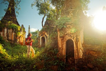 Backpacker traveling and looks at sunset among stupas. Myanmar