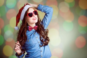 Funny hipster girl in heart shape sunglasses wearing santa hat
