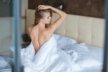 Attractive alluring young woman sitting on bed