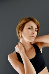 Closeup of fitness girl with neck pain, isolated