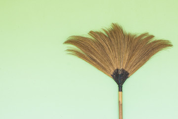 Broom on green background.