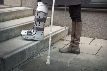 closeup of woman walking with crutches