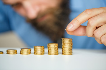 Beared man stacking gold coins into increasing columns