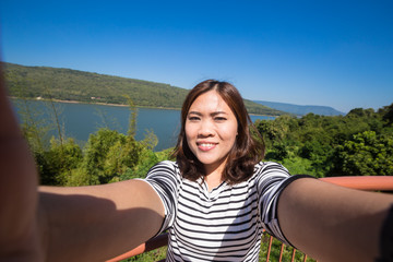 Asian young female tourist makes selfie