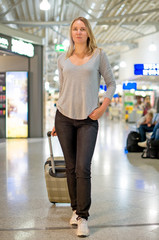 Female passenger walking with travel bag at the airport.