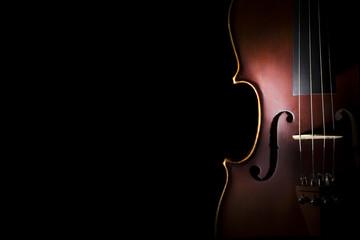 Old violin on black background.