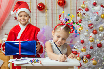 Girl sits at a table with fireworks on the head, Santa Claus is preparing to surprise her