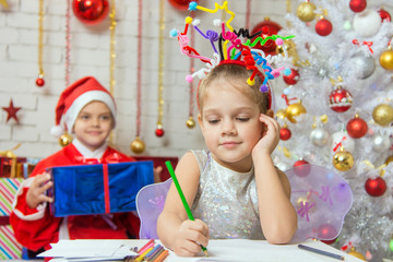 She writes a letter to Santa Claus, who is sitting with a gift behind her