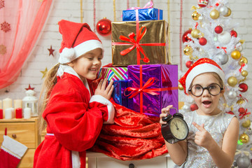 Girl with surprise shows at the clock in the New Year, santa claus smiling happily unpacking gifts