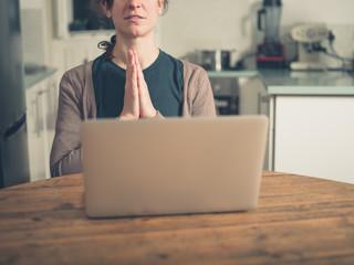 Woman praying by laptop in kitchen