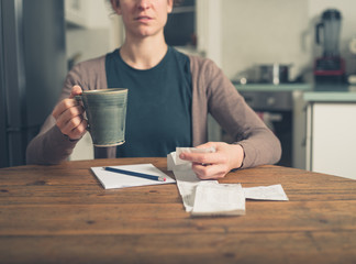 Woman looking at receipts and having tea