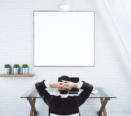 Businessman resting on a chair and looking at blank white pictur