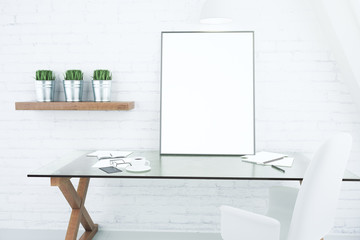 Blank white picture frame on glassy table in modern loft room, m