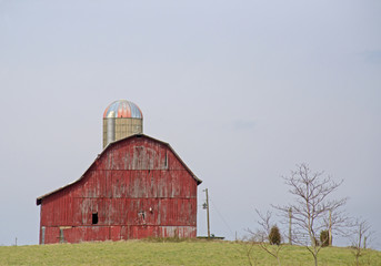 Country red barn with silo at a distance under a blue sky.