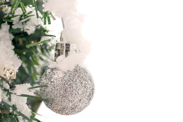 Shiny silver Christmas balls over snow background