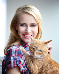 Young woman posing with red cat in hands, close up