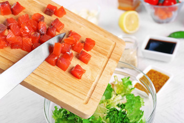 Female hands adding pieces of salmon into bowl with salad, close-up