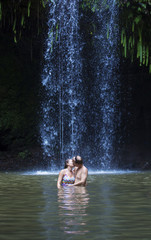 Couple kissing under a beautiful tropical waterfall
